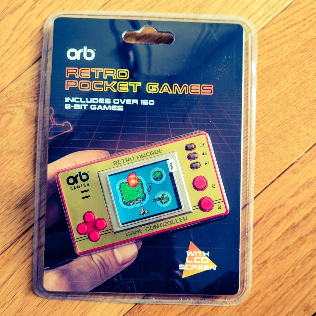 Retro pocket games console in its packet with a wooden floor background