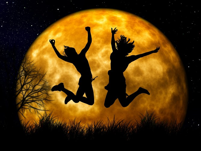 Two women at night jumping in front of a yellow moon.