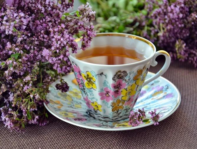 A mug of tea next to purple flowers.