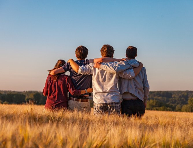 Four teenagers standing with their backs to the camera in a field.