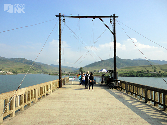 Chinese tourists gaze at North Korea from the end of a broken bridge. | Image: Matthew Bates