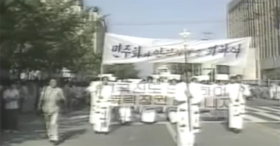 Screenshot from a march during the June Democratic Uprising [6월 민주항쟁]. Many attribute the wave of marches across the country during this month with the decision concede democratic reforms. | Image: Revisiting History(역사다시보기)/YouTube