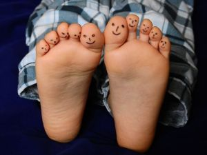 pieds d'un enfant avec des bonshommes dessinés sur les orteils