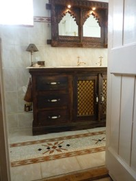 An Indian cupboard has been custom made into a vanity unit in this bathroom.