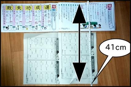 学校の学習プリントと漢字ドリルを並べてサイズを測った写真
