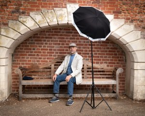 A man in a white jacket having his photograph taken in waterlow park with studio lighting.