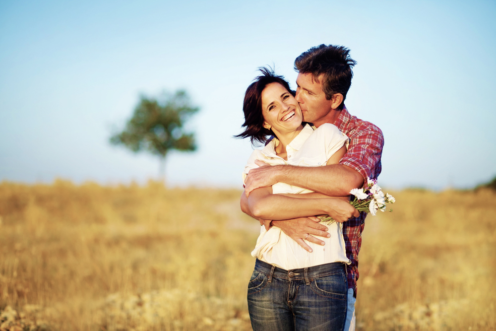 couple embracing in a field