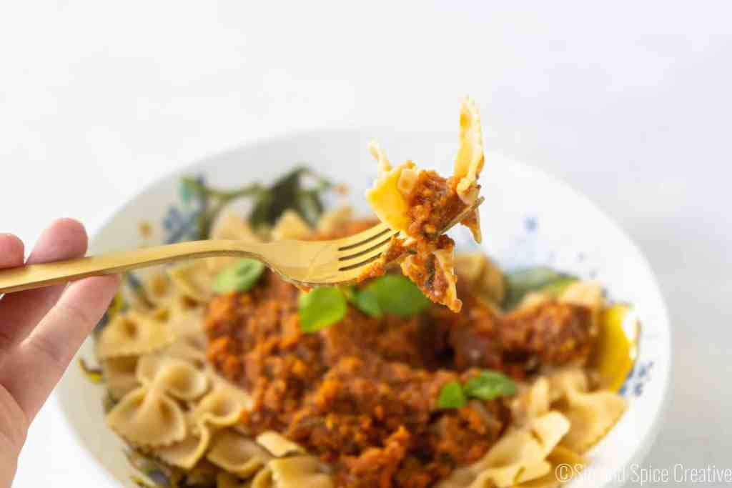 Final Image with Forkful in the air Veggie Bolognese with Fresh Basil on Chickpea Pasta | Sip and Spice