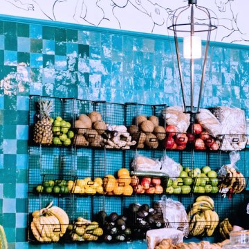 Create a cozy kitchen with Cast Iron display ideas like this teal tile wall and hanging cast iron fruit baskets