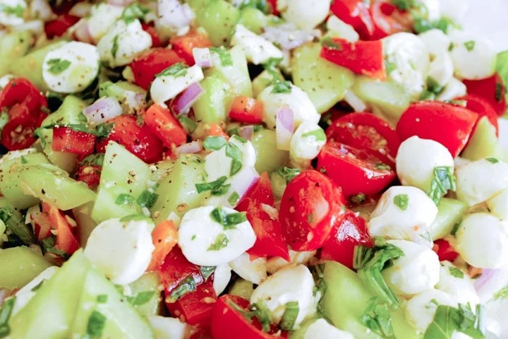 closeup shot of caprese salad recipe ingredients with mozzarella balls cucumber tomato and basil