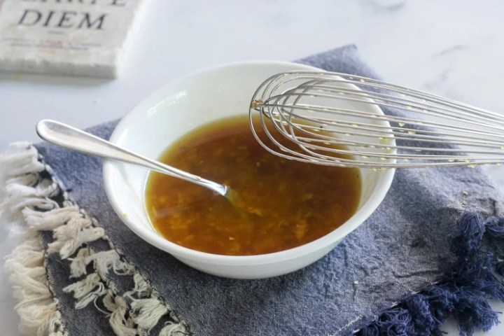 whisking together garlic vinaigrette