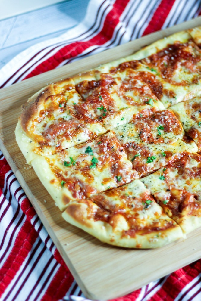 homemade pizza dough cut in square slices on a red and white kitchen towel and cutting board