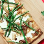 overhead shot of asparagus pizza with pesto, mozzarella, and caramelized onions
