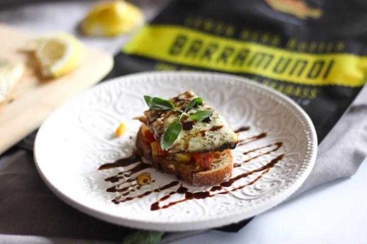 baked barramundi fish toast appetizer on top of a bag of lemon flavored Australis Barramundi