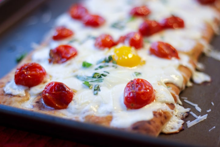 Closeup of breakfast pizza made in the oven on a sheet pan