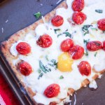 overhead shot of breakfast pizza with eggs tomatoes basil and parmesan cheese