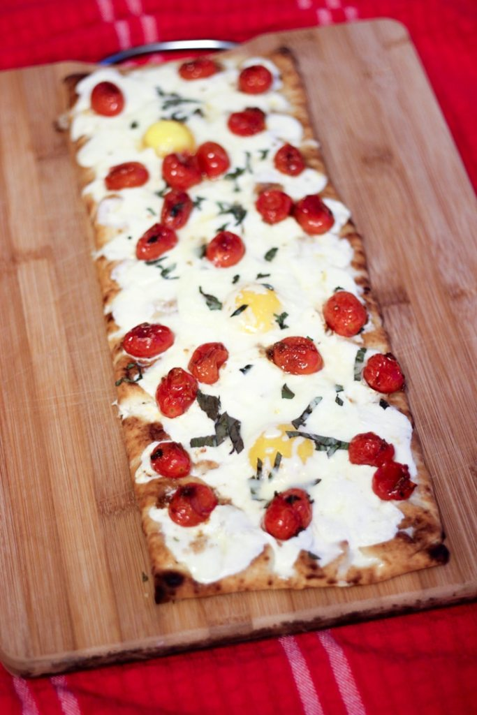 Baked breakfast pizza with premade crust on a cutting board