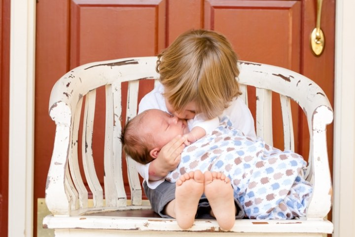 Baby sleeping in a swaddle while his older brother holds him on a chair