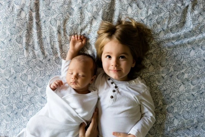 Baby sleeping in white swaddle next to a sister