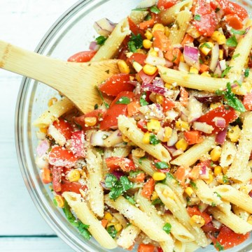 Mexican pasta salad with chili lime dressing in a serving bowl with wooden spoon