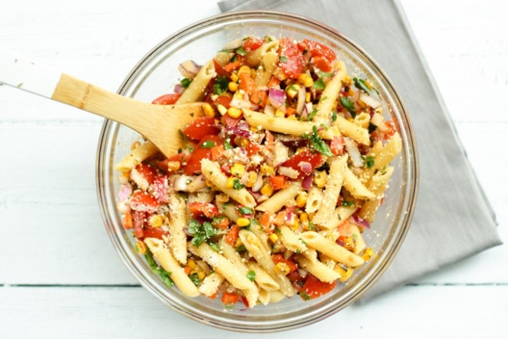 overhead process shot of Mexican pasta salad with chili lime dressing in a large glass bowl with gray napkin