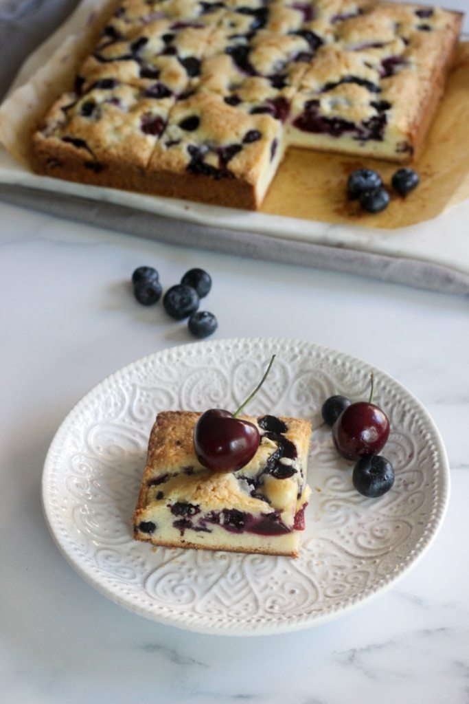 serving fresh blueberry and cherry cake bars on a white plate