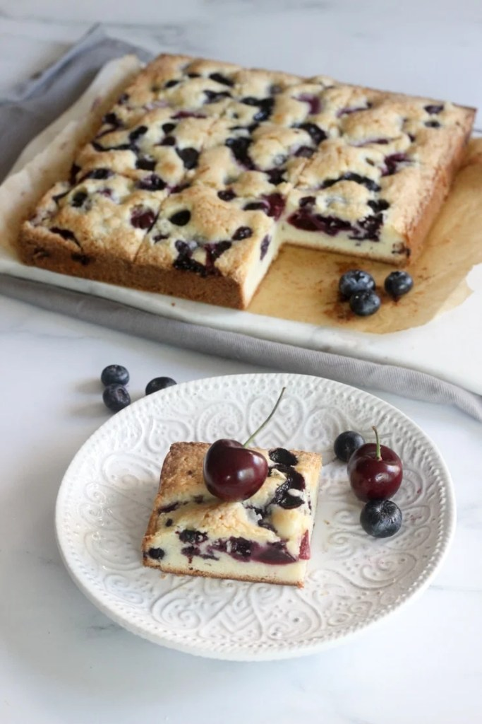 these fresh blueberry and cherry cake bars on a table