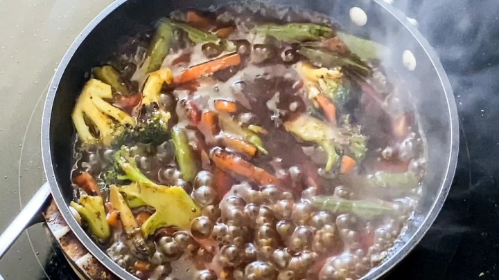Asian sauce packet bubbling in stir fry with frozen vegetables