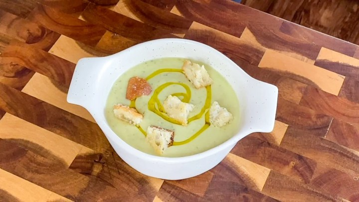 serving chilled zucchini soup with crouton toppings