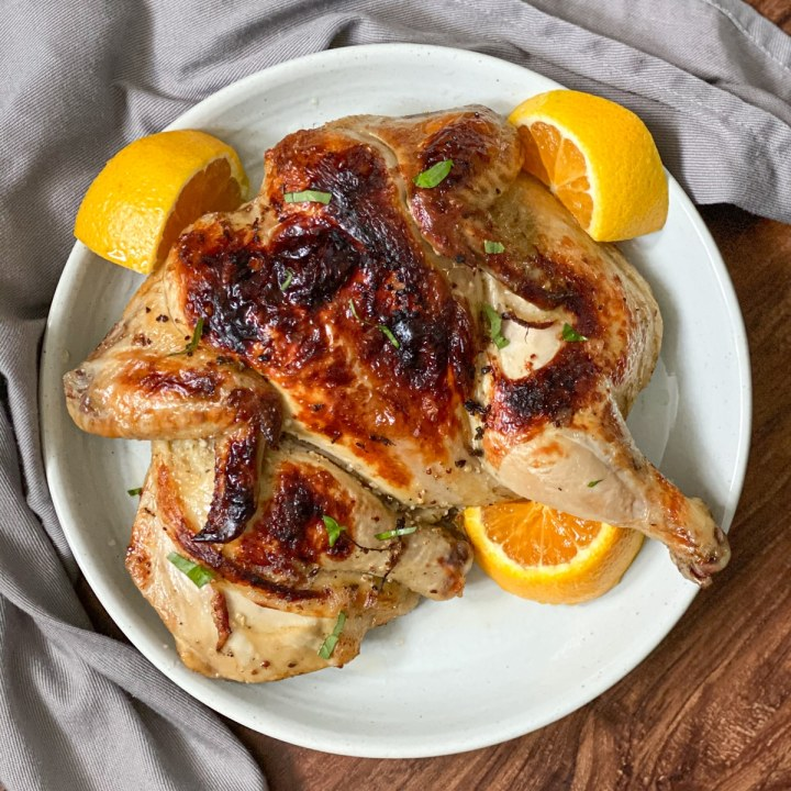 serving sous vide roast chicken on a plate with oranges feature