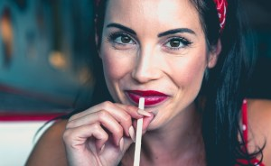 Girl with red lipstick sipping from straw