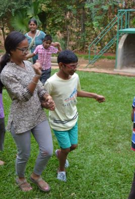 """Akil and I dance to """"Chai Chai, Coffee Coffee"""" during movement time at Bubbles' Summer Camp. The sensory experience of music and movement is both therapeutic and instructive for children with Autism and it is thus incorporated into their daily schedule."""