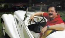 Pak Hauwke berfoto dengan salah satu mobil kuno kesayangannya.