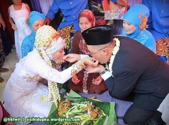 Kedua pengantin saling menyuapi.