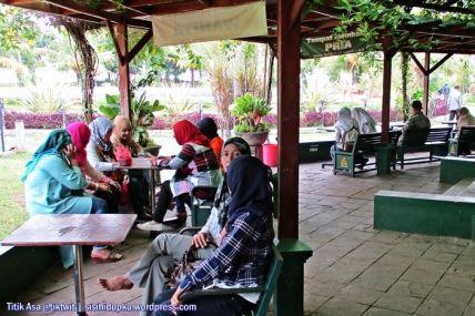 Duduk dan mengobrol pada bangku di teras Taman Bacaan