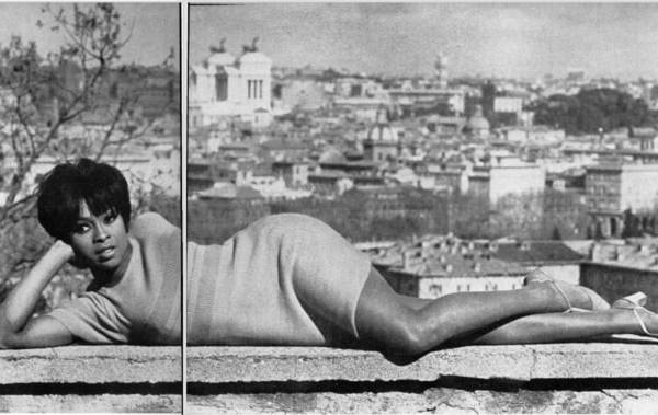 Lola Falana poses lying down with a cityscape in the background. It's a sunny day.