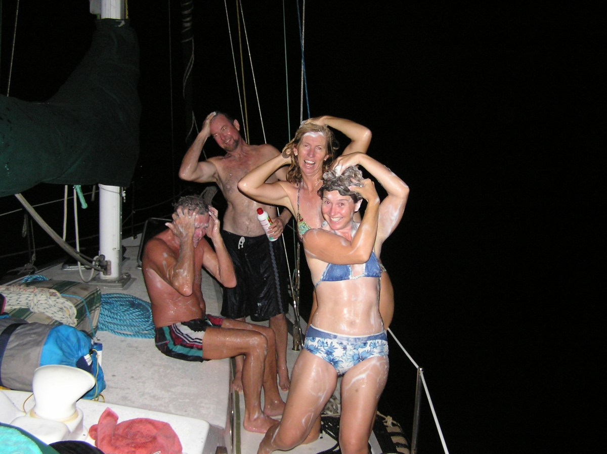 The crew of Theta on the deck at night, taking advantage of the fresh water with lots of shampoo
