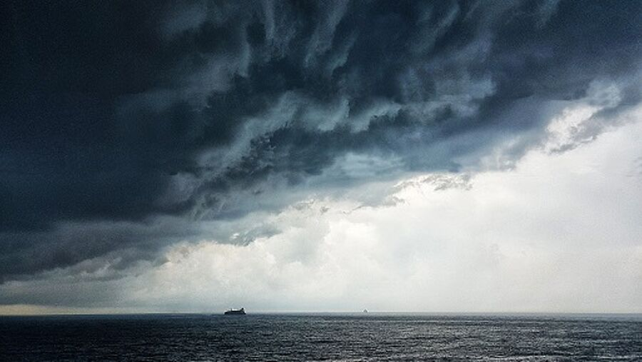 Large angry black clouds gather above the sea