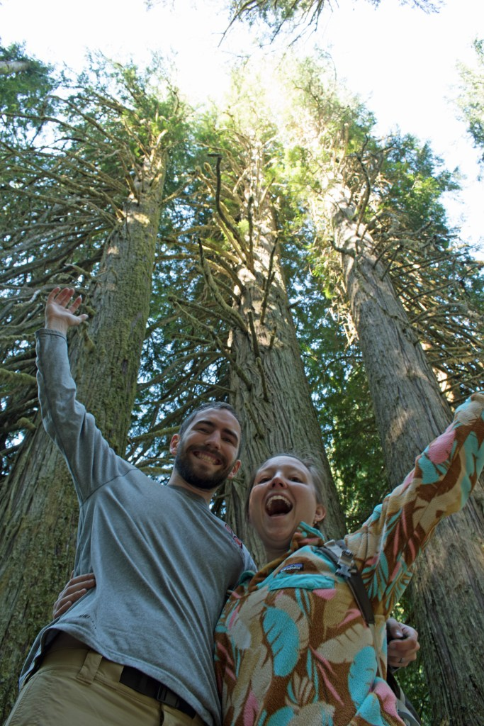 Two people with their arms around each others' shoulders and raising the other arm towards the big trees behind them.