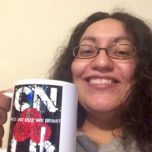 A smiling person holds up a coffee cup with the letters CNLD on it.