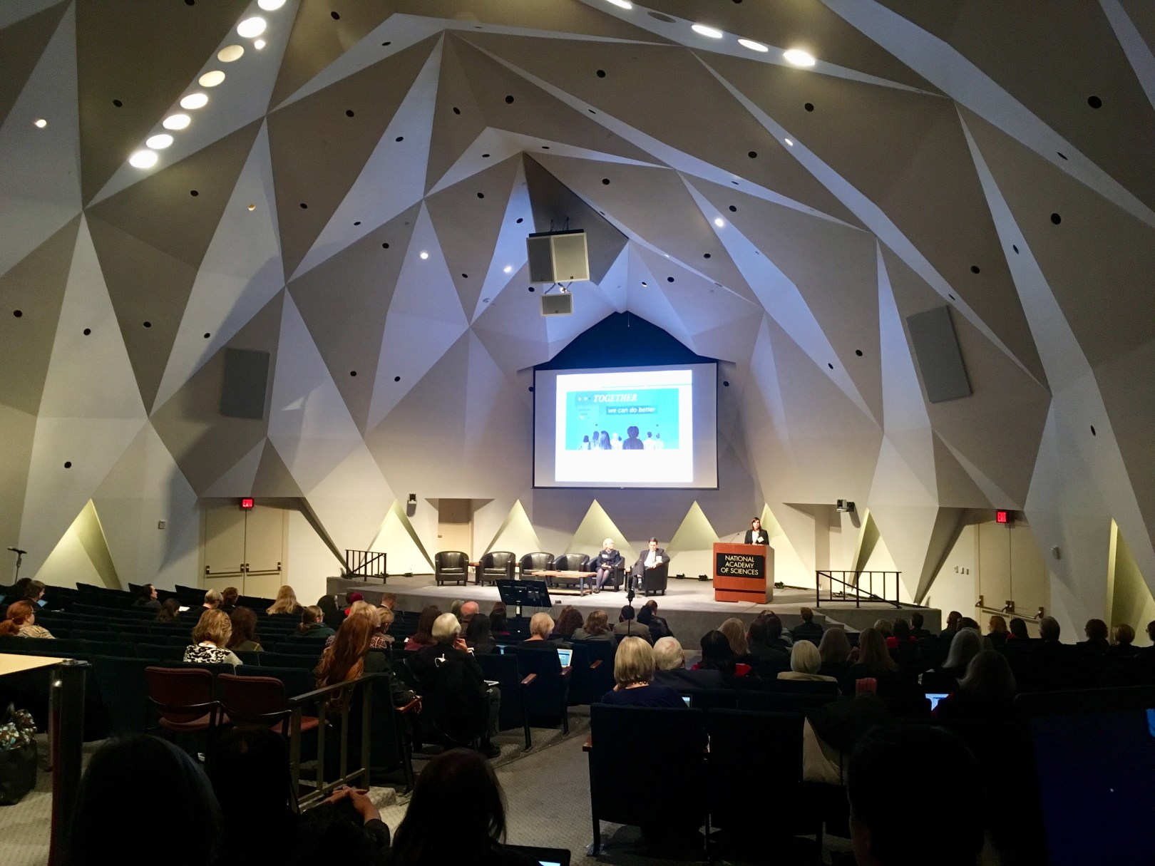 People fill a modern-looking auditorium. There are three people on stage, two seated and one at a podium, and a title slide of a presentation is displayed on a large screen.