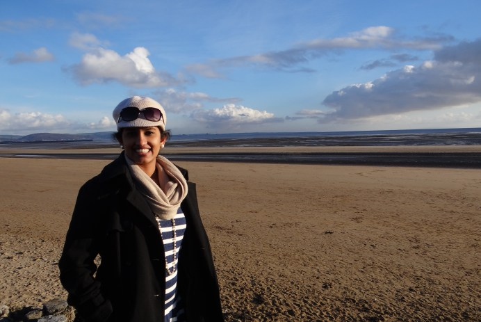 A photo of the author -- she stands smiling in front of a landscape and a sunny blue sky, with a scarf, coat, and hat on.