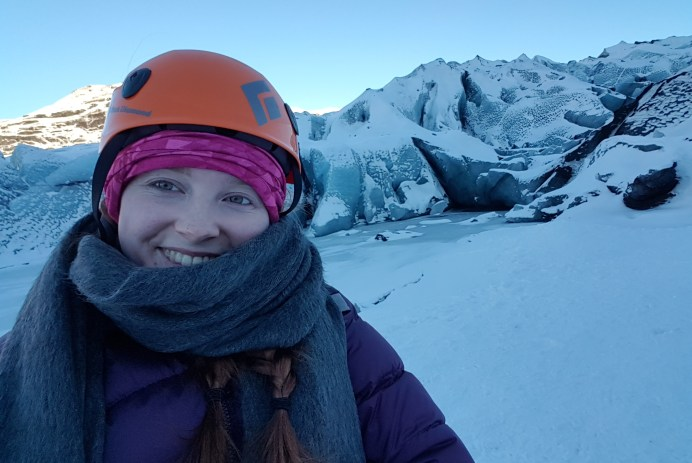 The author is smiling, bundled up in a puffy coat, scarf, and helmet, on the Sólheimajökull glacier in Iceland in January 2019. There is a an icy blue glacier in the background.