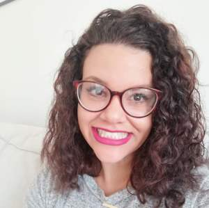 Close-up of the author, who is smiling and wearing glasses, pink lipstick, and curly shoulder-length hair.
