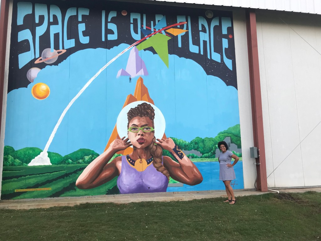 "Charnell stands in front of a mural depicting Taraji P. Henson as Katherine Johnson from the movie Hidden Figures and the words ""Space is our place"" across the top of the mural."
