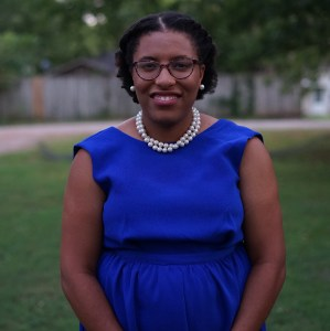 Professional photo of the author standing outside in a royal blue dress, pearl necklace and earrings, and glasses.