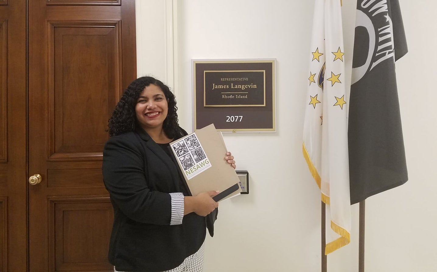 The author outside of Rep. James Langevin's office in Congress, holding up her advocacy day materials.