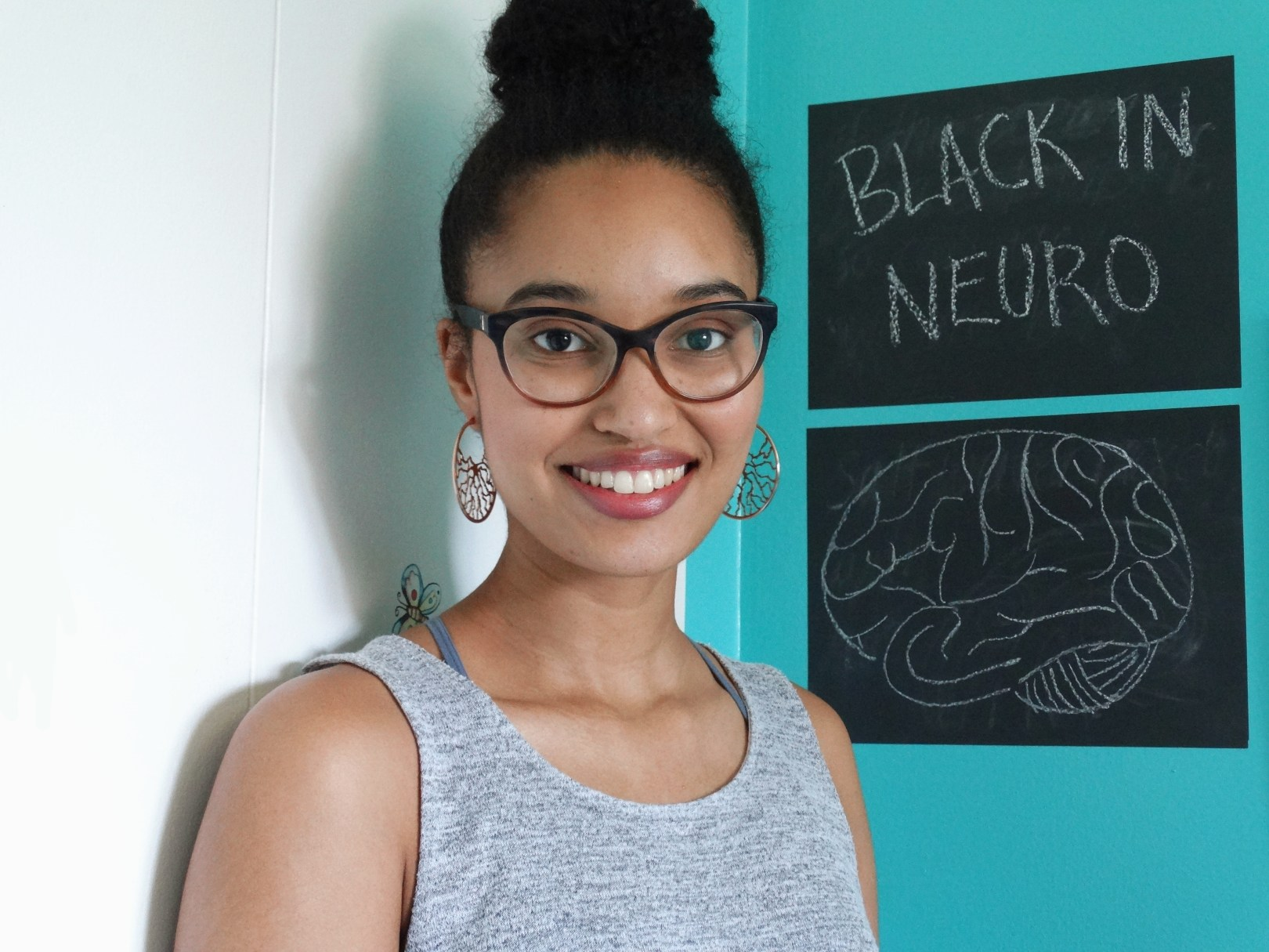 Danielle is looking at the camera, smiling wide in front of a chalkboard featuring a drawing of a brain. Text reads: Black In Neuro