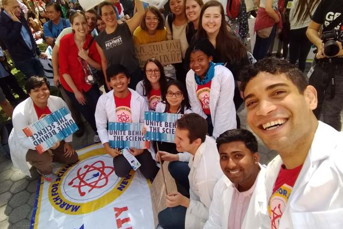 "A group of scientists in lab coats, holding signs that say ""Unite behind the science."""