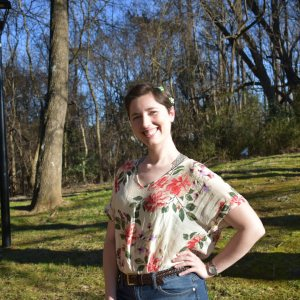 Maggie Swift is standing outside, smiling with her hand on her hip, wearing a floral top.